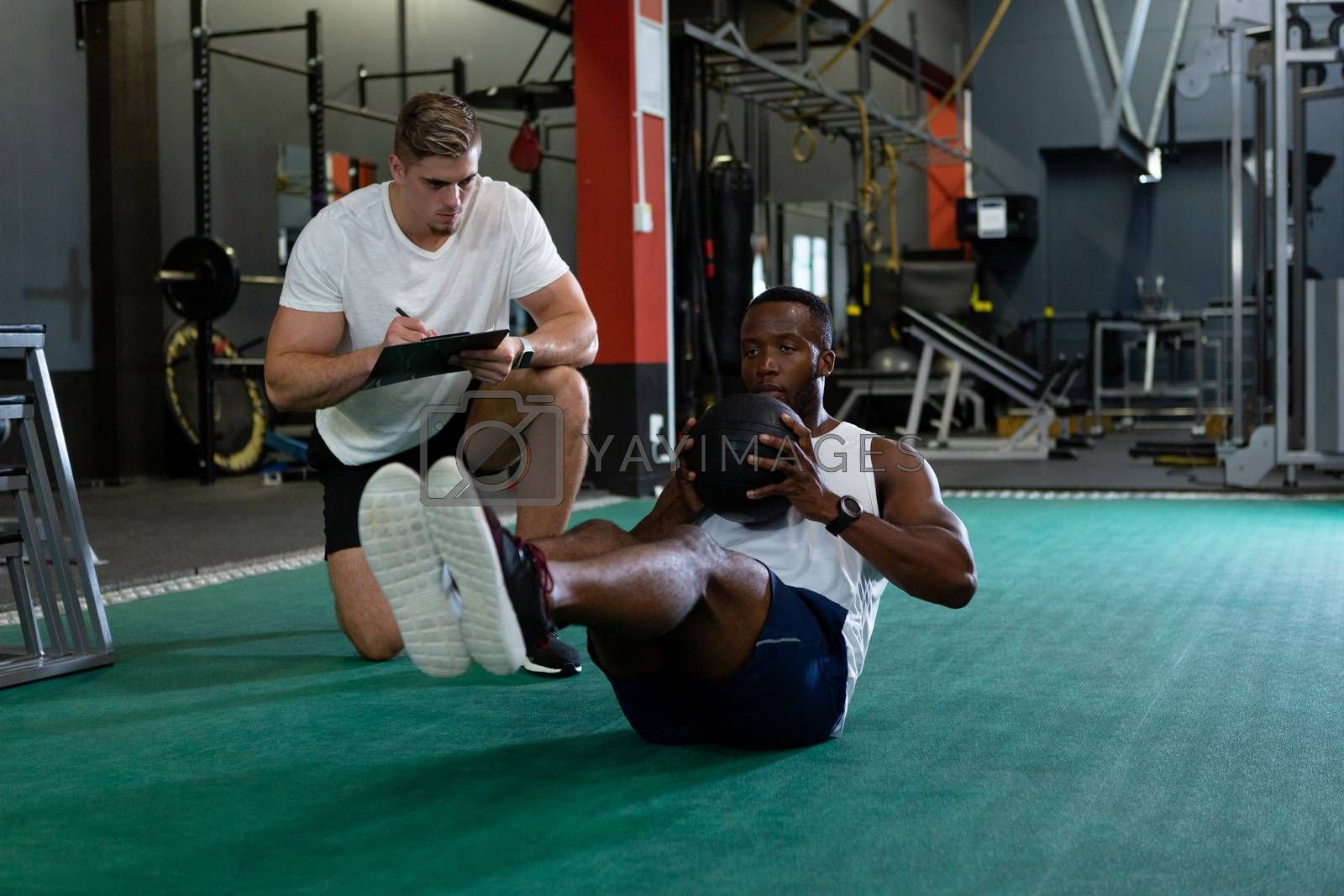 Front view of handsome young Caucasian male trainer writing on clipboard while young fit African-american male athletic exercising with exercise ball in fitness center. Bright modern gym with fit healthy people working out and training