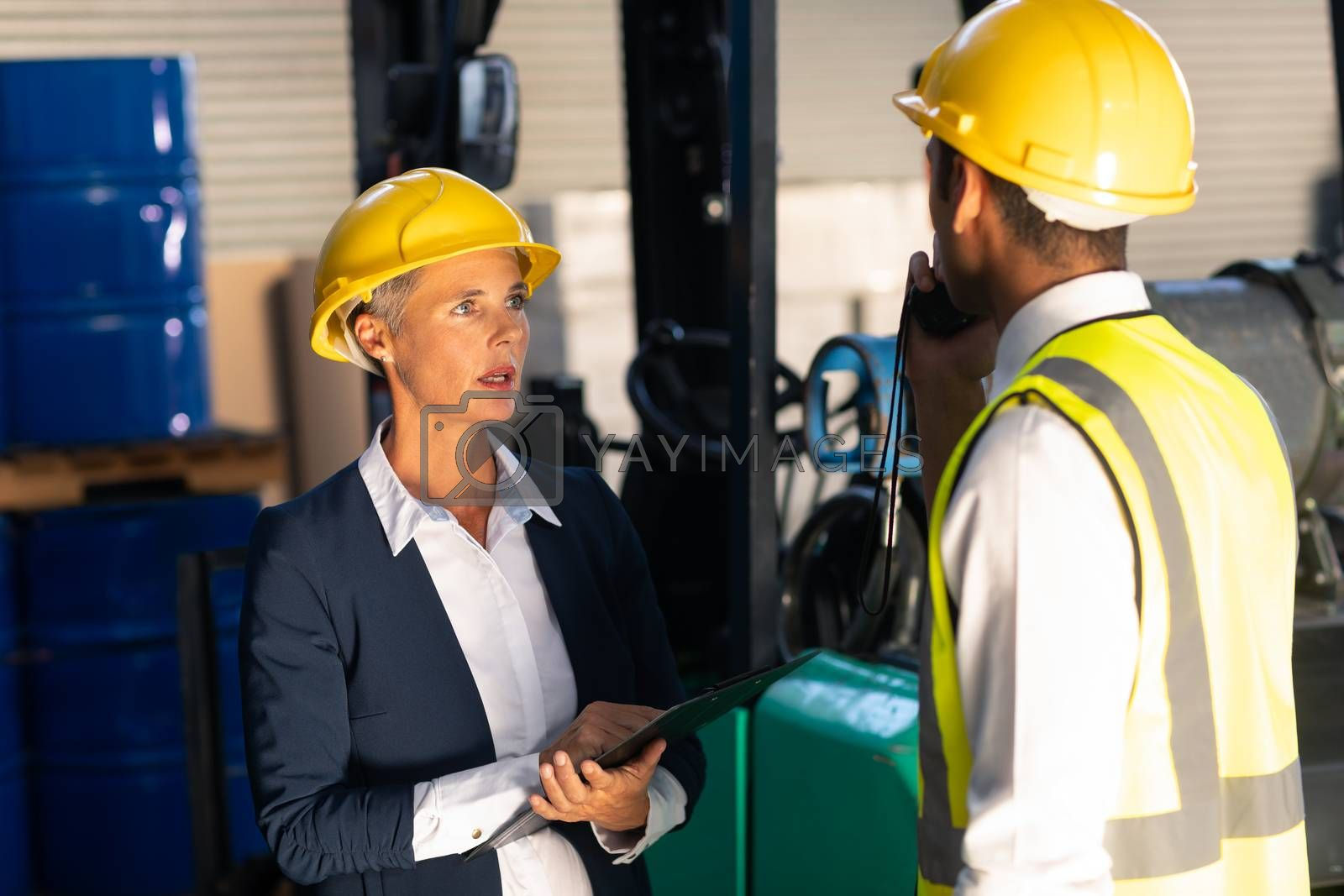 Front view of Caucasian female manager and Caucasian male supervisor interacting with each other in warehouse. This is a freight transportation and distribution warehouse. Industrial and industrial workers concept