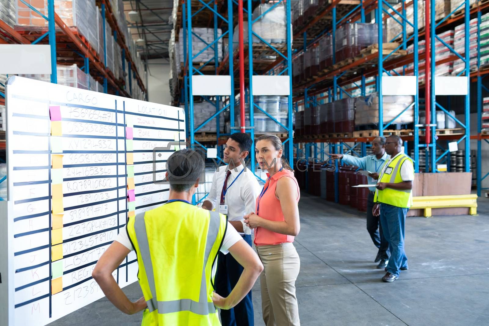 Front view of diverse warehouse staffs interacting with each other in warehouse. This is a freight transportation and distribution warehouse. Industrial and industrial workers concept