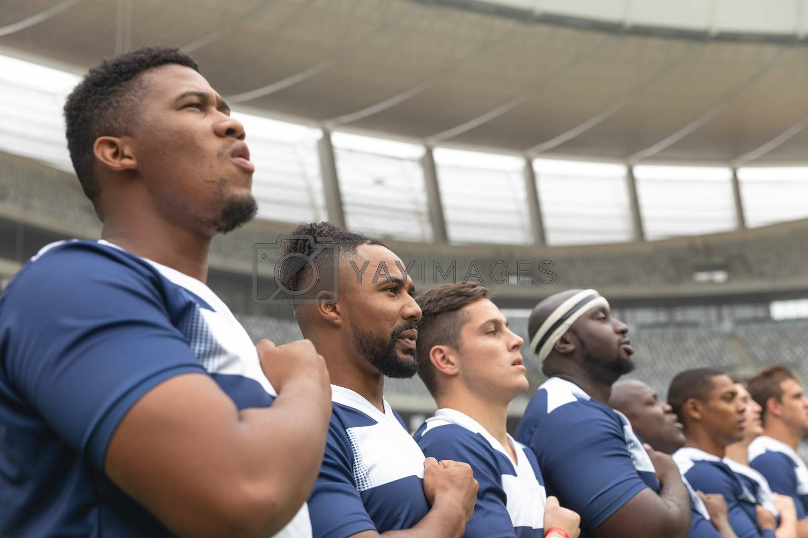 Portrait of group of diverse male rugby players taking pledge together in stadium
