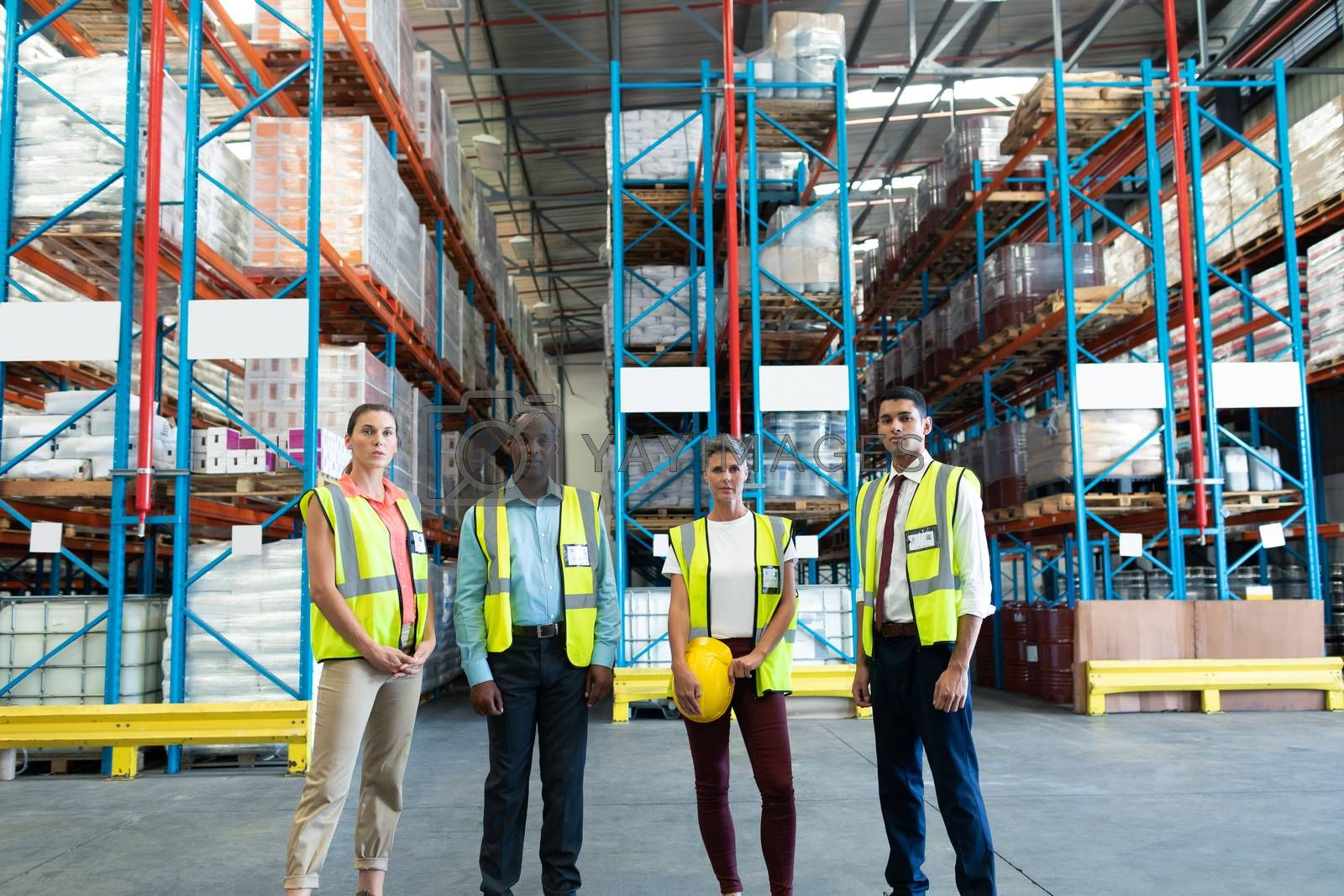 Front view of diverse warehouse staffs standing together in warehouse. This is a freight transportation and distribution warehouse. Industrial and industrial workers concept