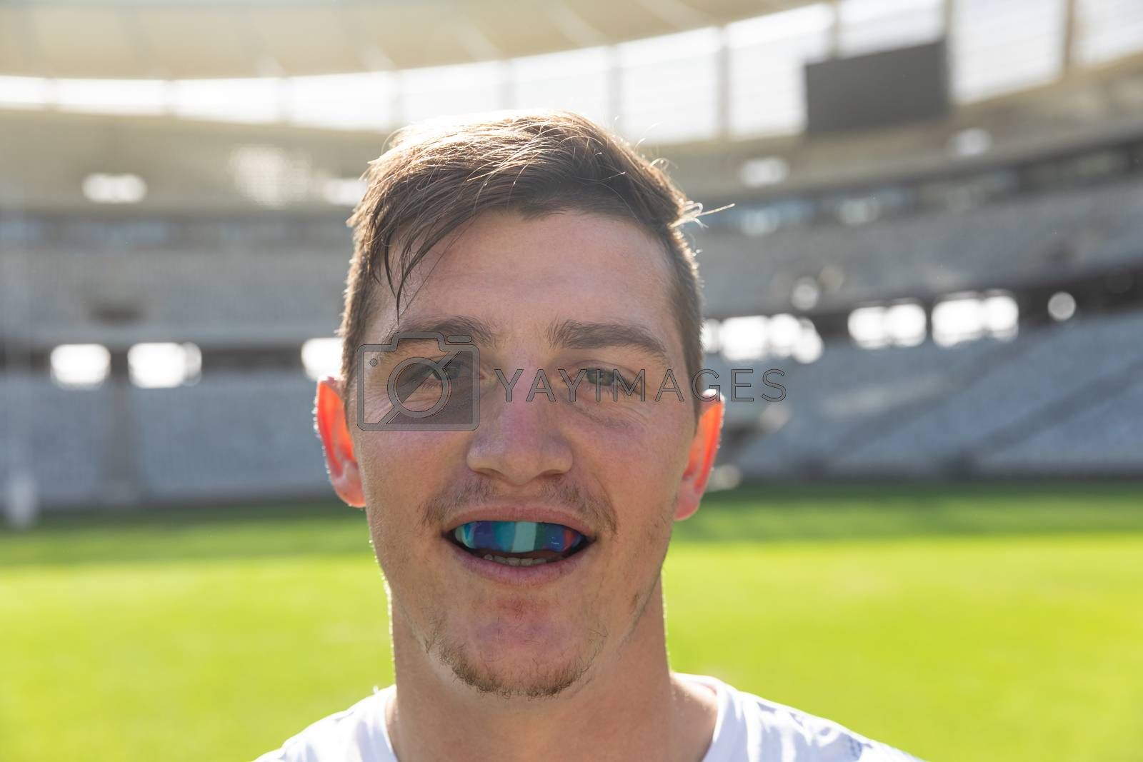 Portrait close up of Caucasian male rugby player with mouth guard in stadium on sunny day.