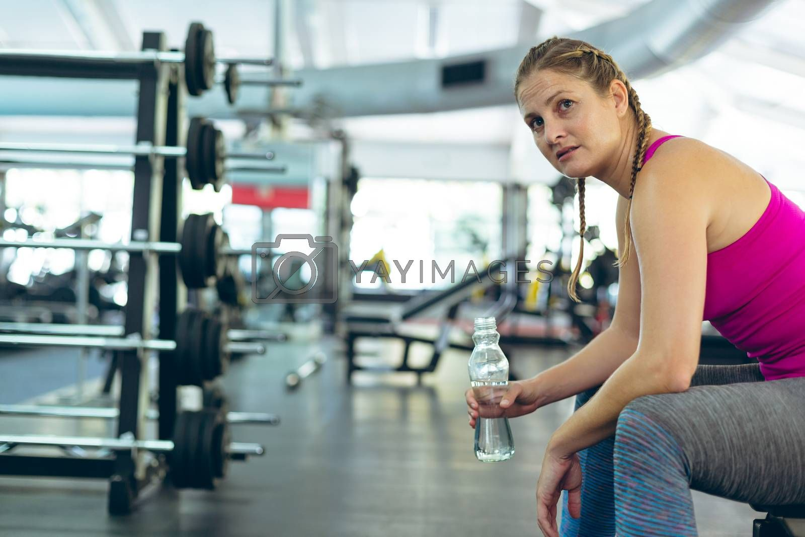 Side view of young fit Caucasian female athletic having water while relaxing on a bench in fitness center. Bright modern gym with fit healthy people working out and training
