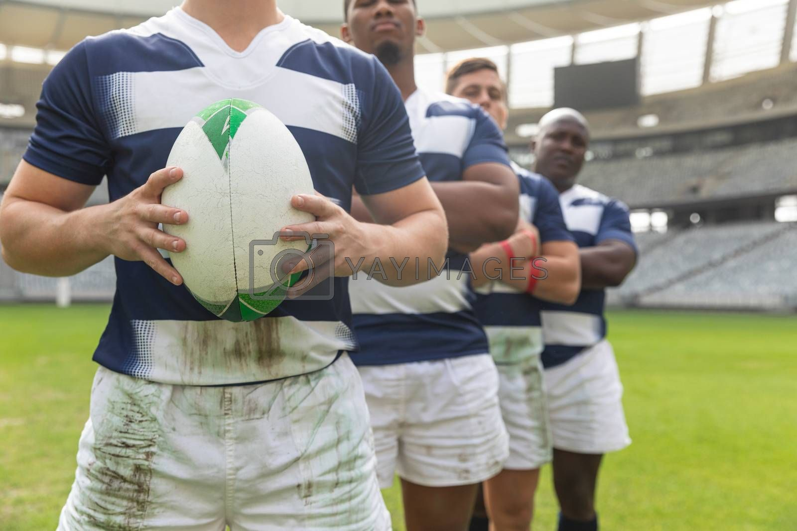 Mid section close up of diverse male rugby players standing with arms crossed together with rugby ball in stadium.