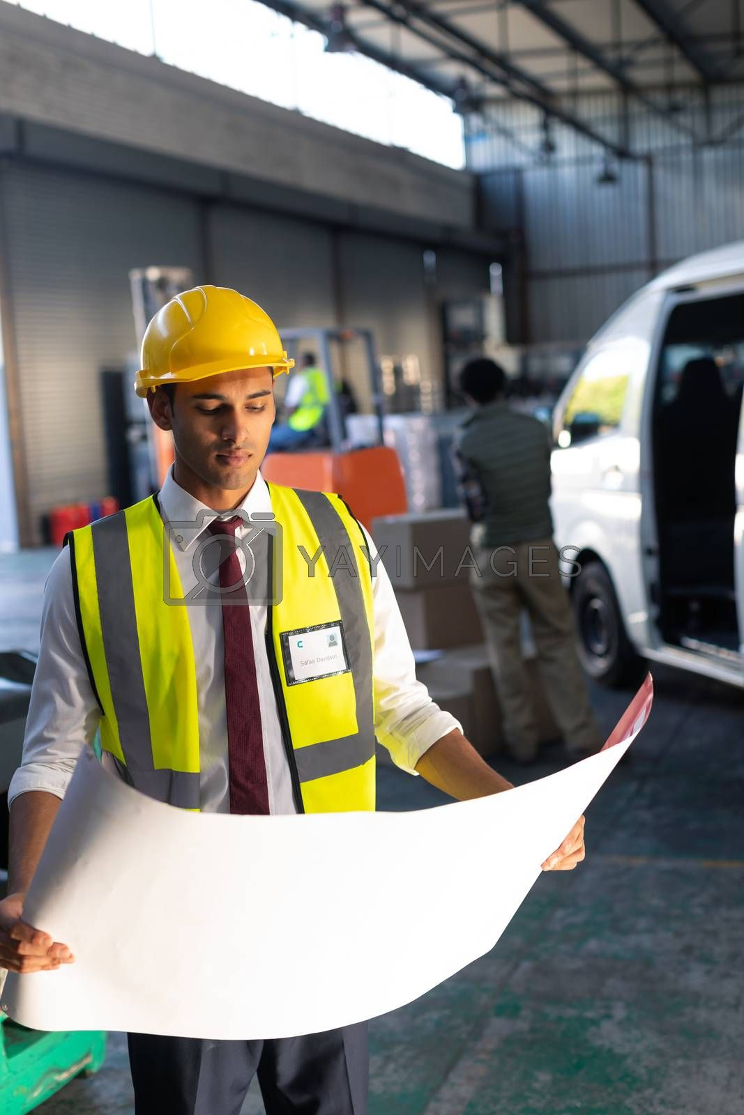 Front view of Caucasian male supervisor looking at blueprint in warehouse. This is a freight transportation and distribution warehouse. Industrial and industrial workers concept