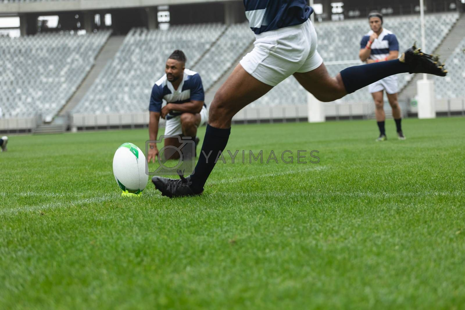Low section of African American male rugby player kicking rugby ball in stadium. With players in the background.