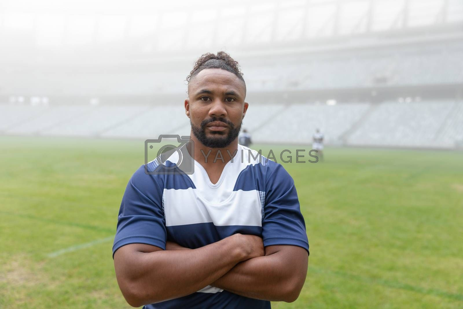 Portrait of African american rugby player standing with arms crossed in the stadium. With players in the background.