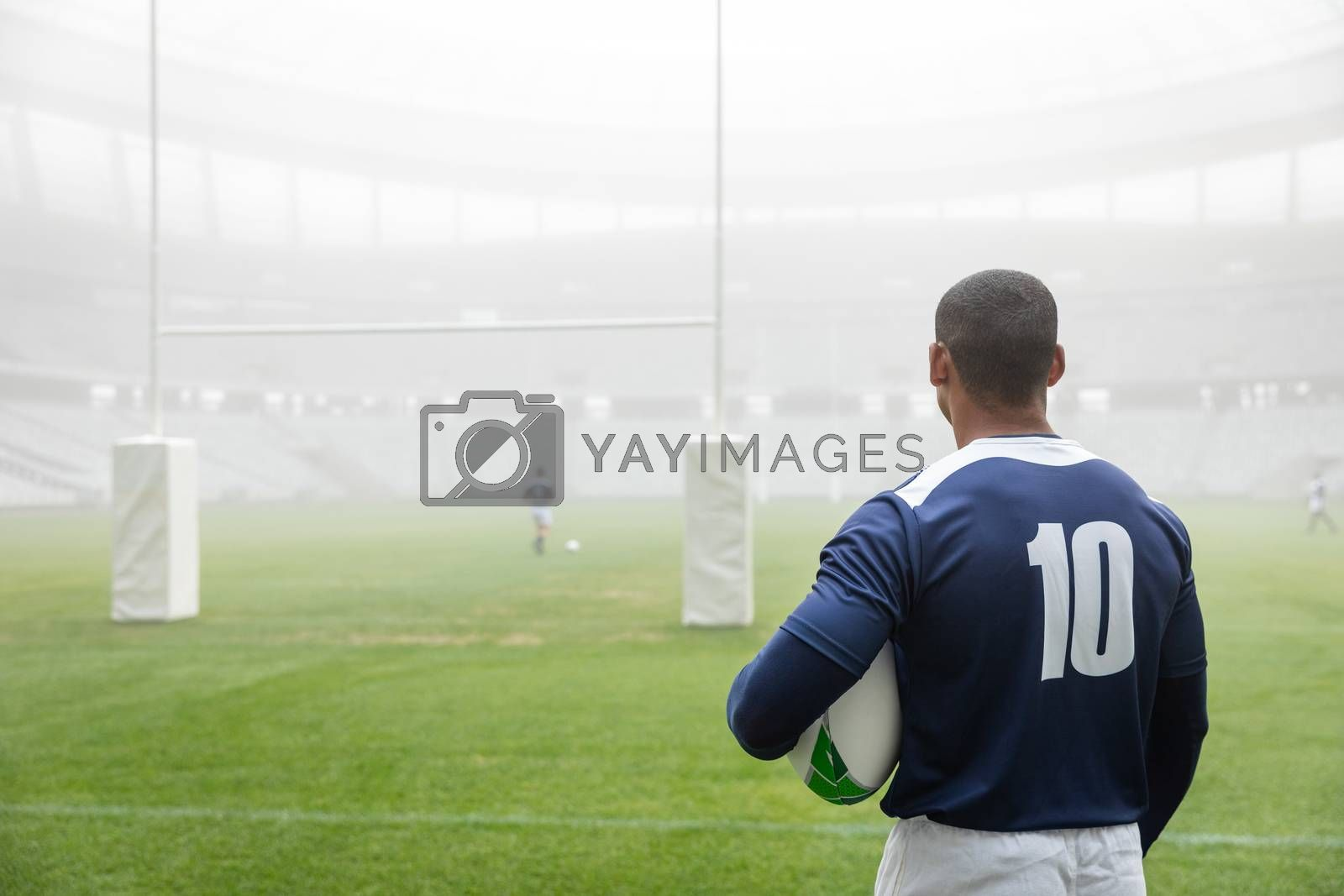 Rear view of thoughtful African american male rugby player standing with rugby ball in stadium