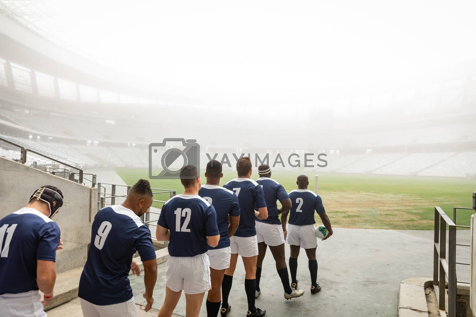 Rear view of diverse male rugby players standing at the entrance of stadium in a row for match