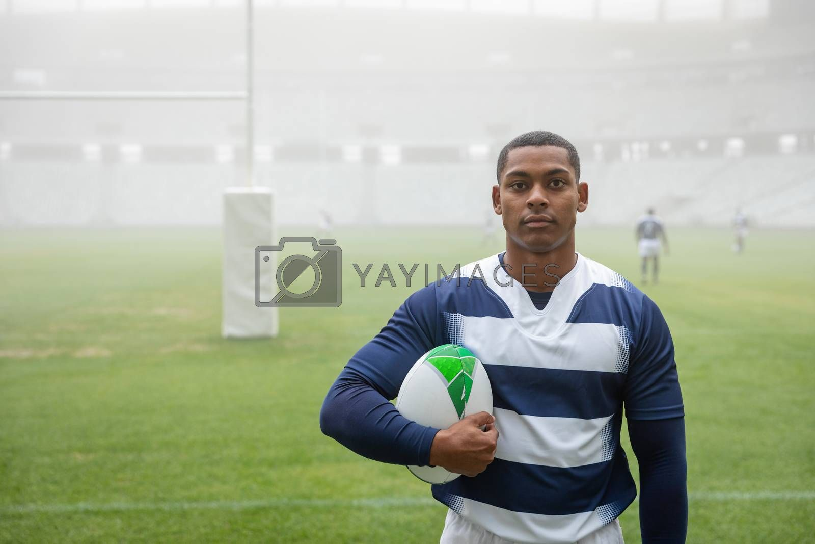 Portrait of African american male rugby player holding a rugby ball in stadium. With players in the background.