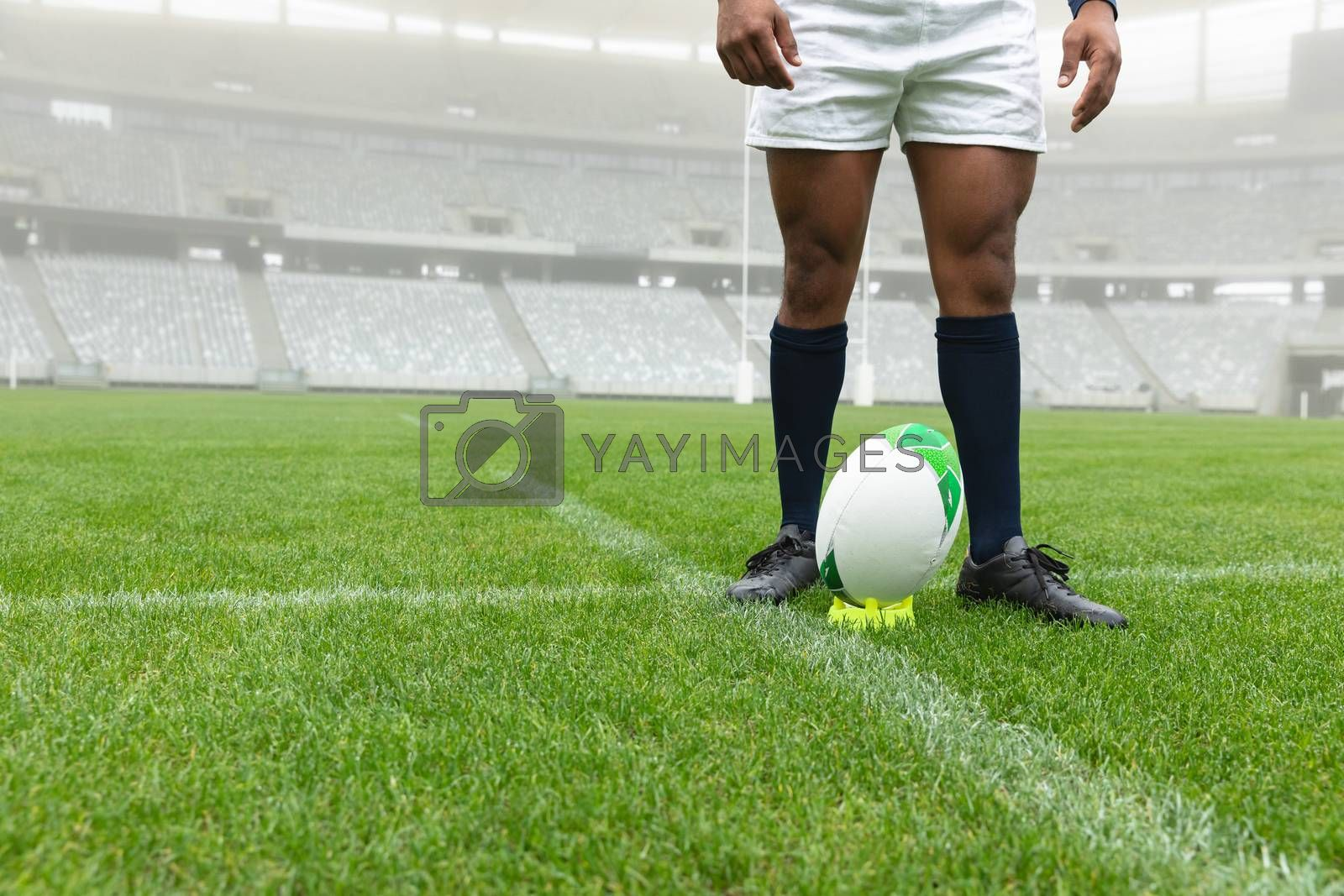 Low section of African American male rugby player standing near rugby ball in stadium