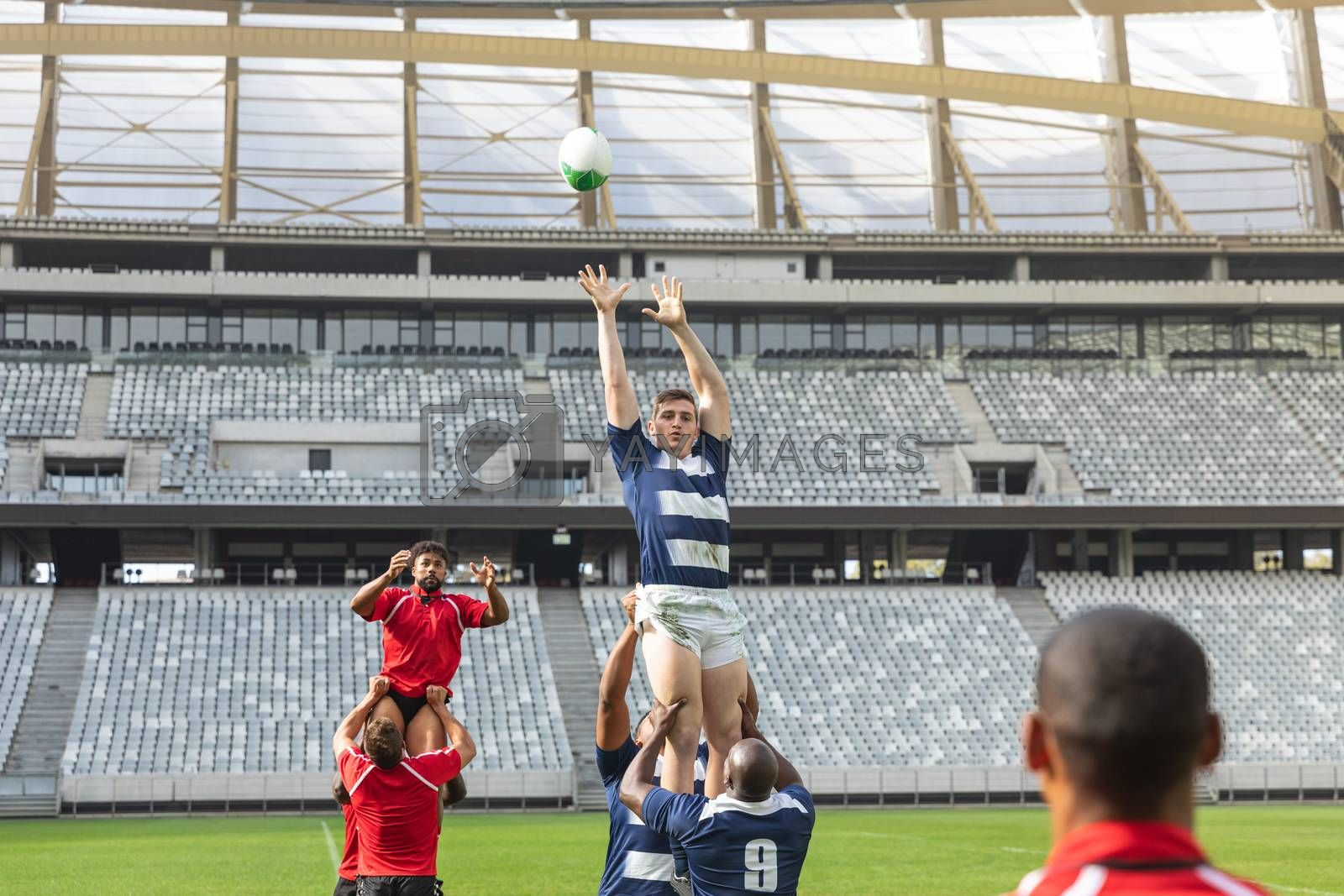 Front view of Caucasian male rugby player and African American rugby player trying to catch the ball in the air while team members help them in stadium on sunny day.