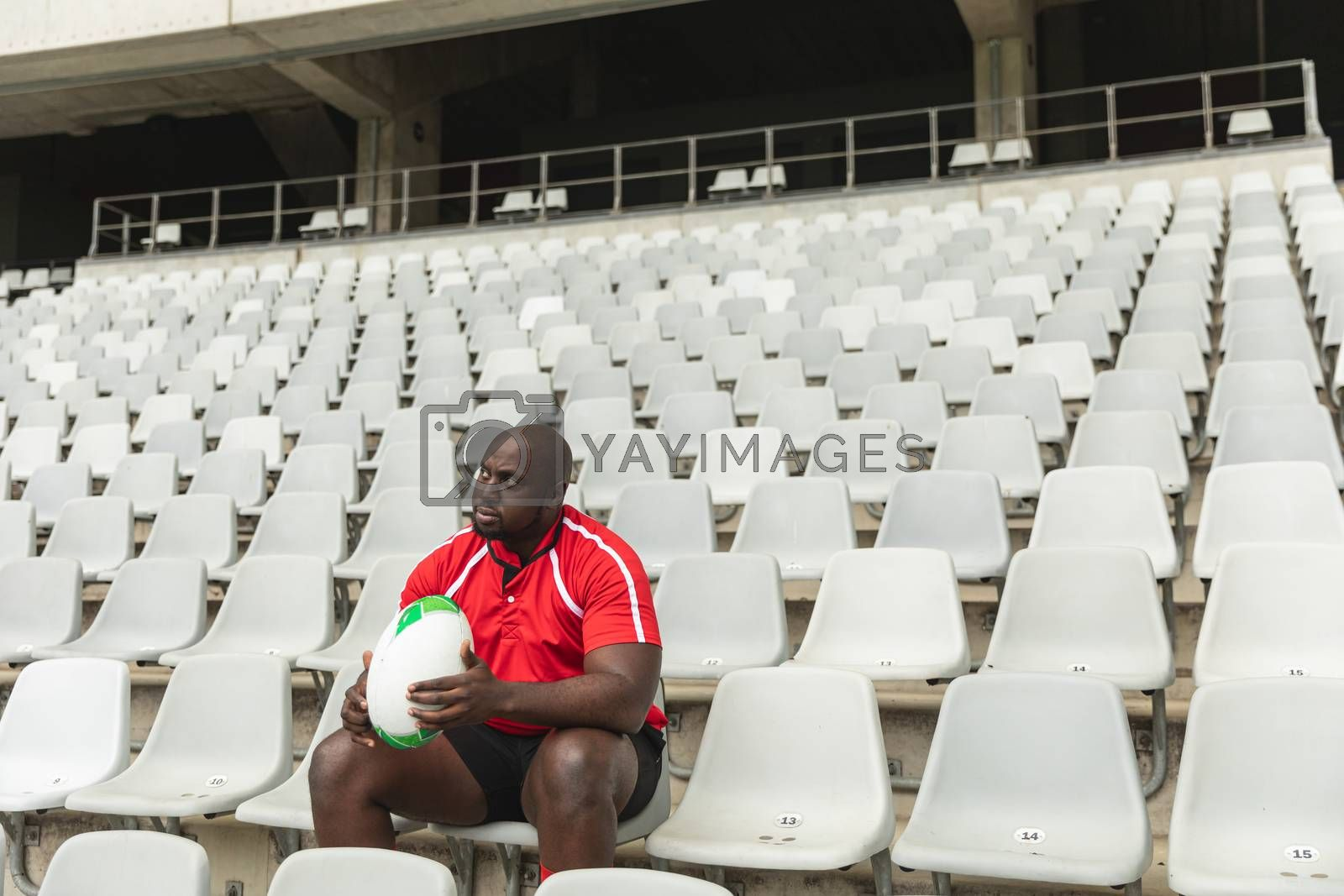 Side view of upset African American male rugby player sitting with rugby ball in stadium