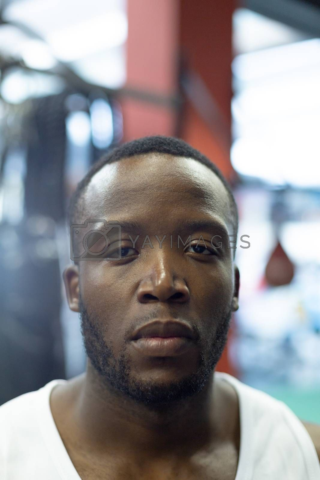 Portrait close-up of handsome fit African-american man looking at camera in fitness center. Bright modern gym with fit healthy people working out and training