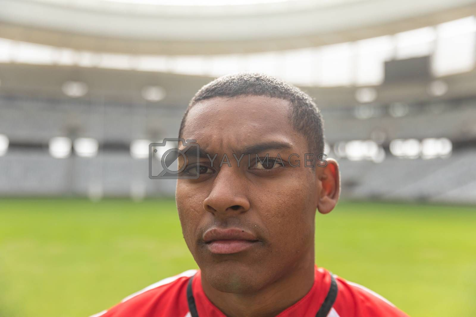 Portrait close up of handsome African American rugby player looking at camera in the stadium on sunny day.