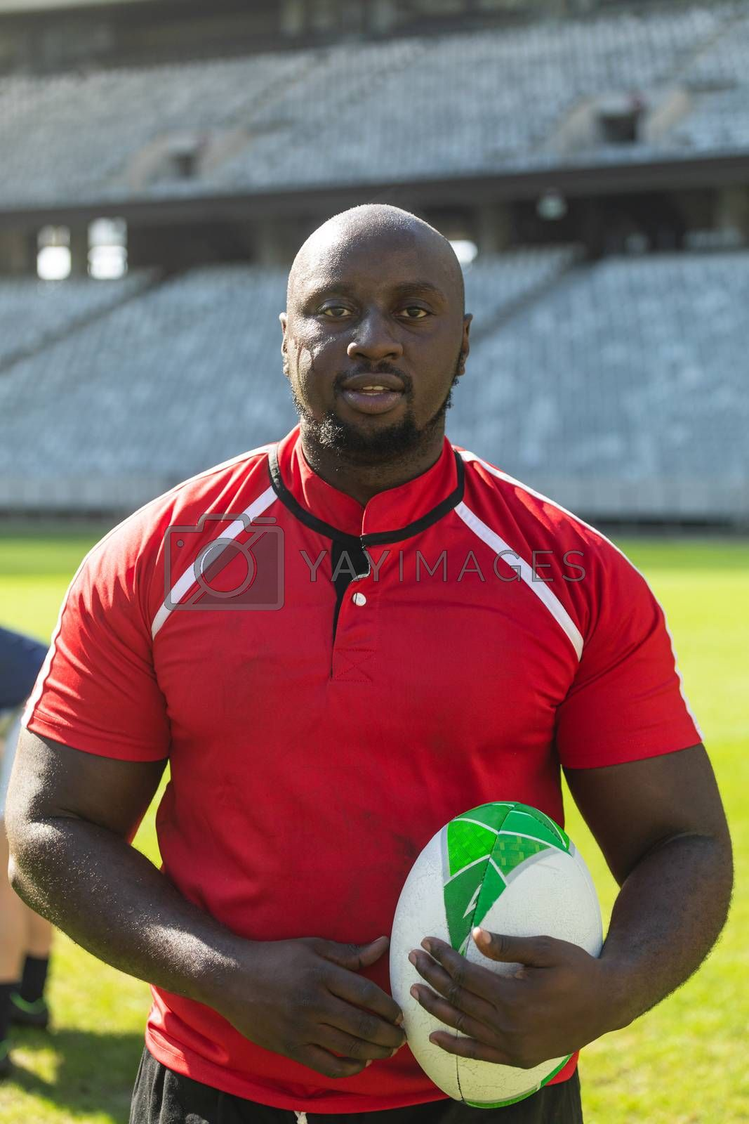 Portrait close up of handsome African American rugby player standing with rugby ball in the stadium on sunny day.