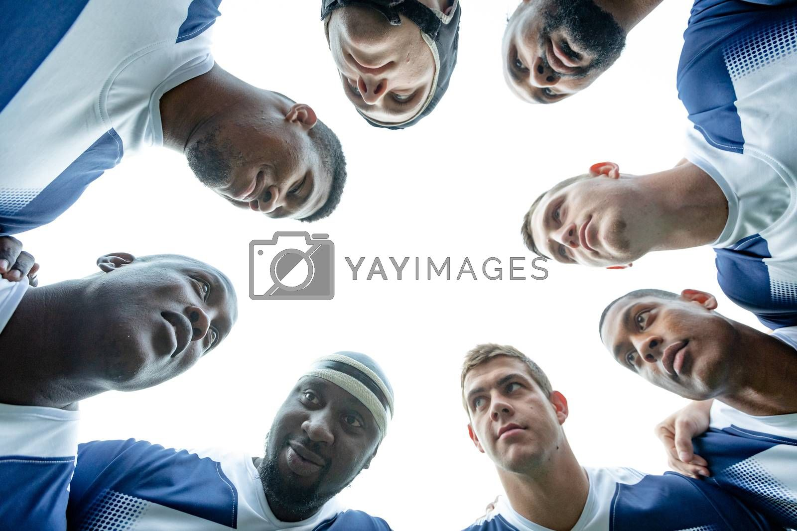 Bottom view of group of male rugby players forming huddles in stadium