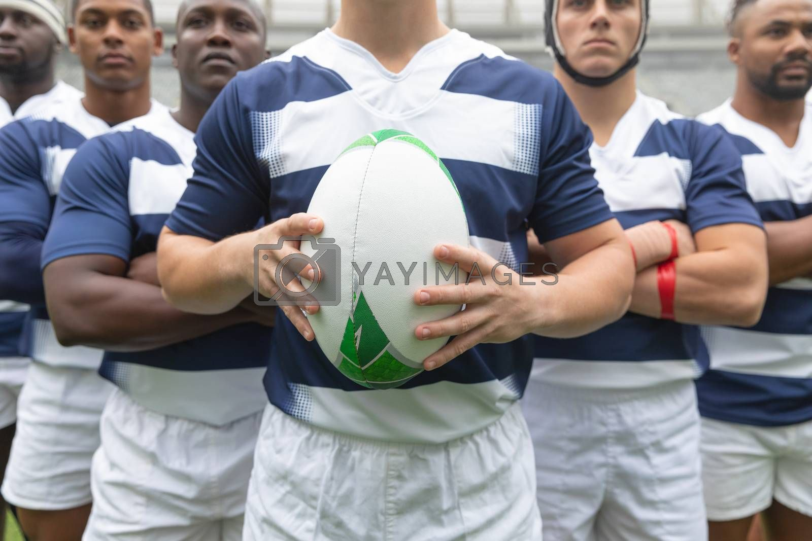 Mid section of group of male rugby players standing together with rugby ball in stadium