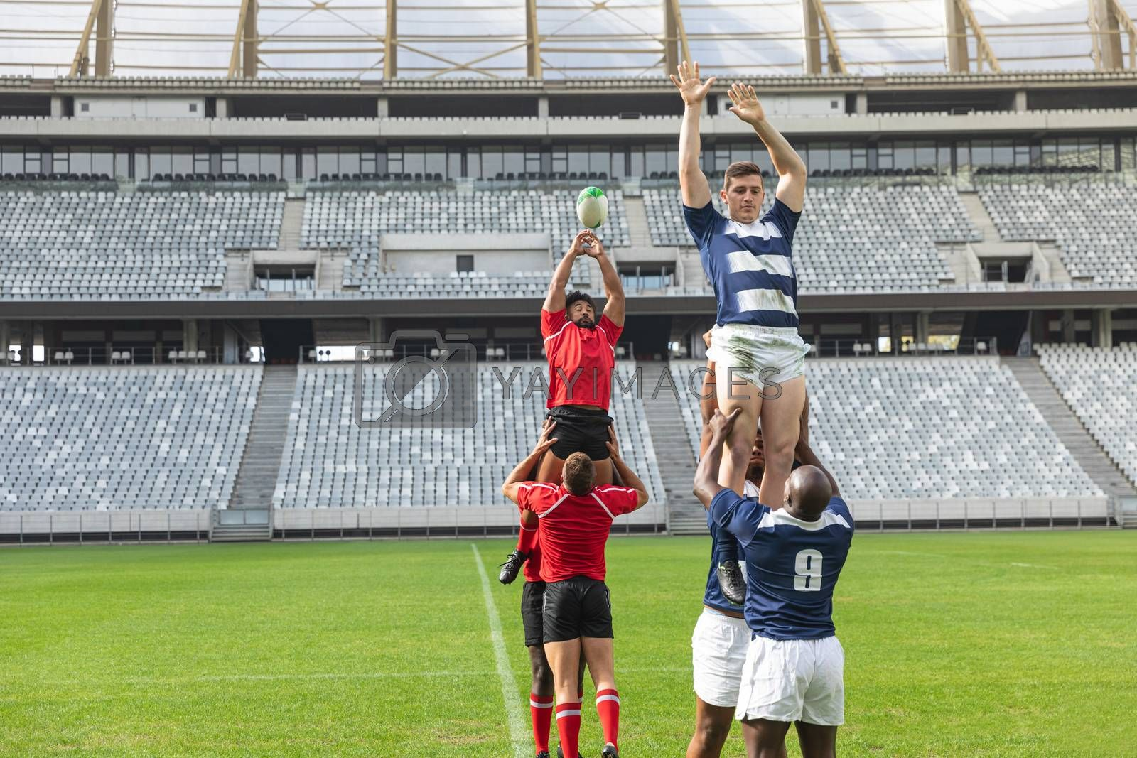 Front view of group of diverse male rugby players playing rugby match in stadium. African American player and Caucasian player are trying to catch the ball in the air.
