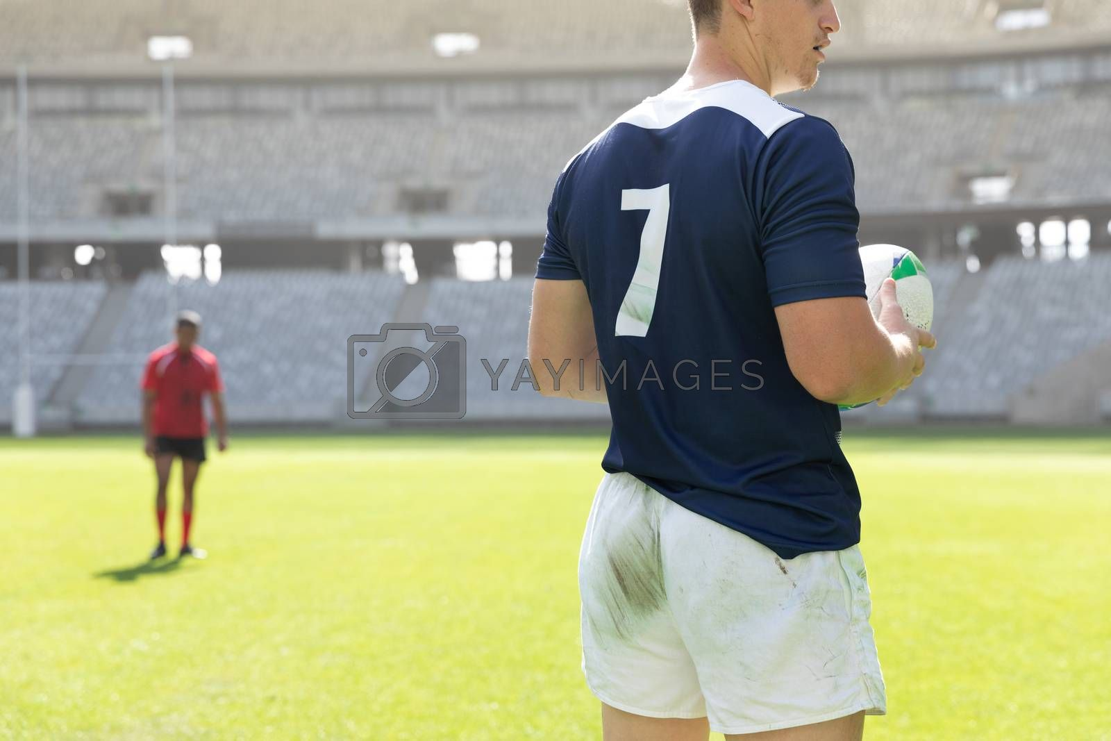 Mid section close up of handsome Caucasian male rugby player holding a rugby ball in the stadium on a sunny day.