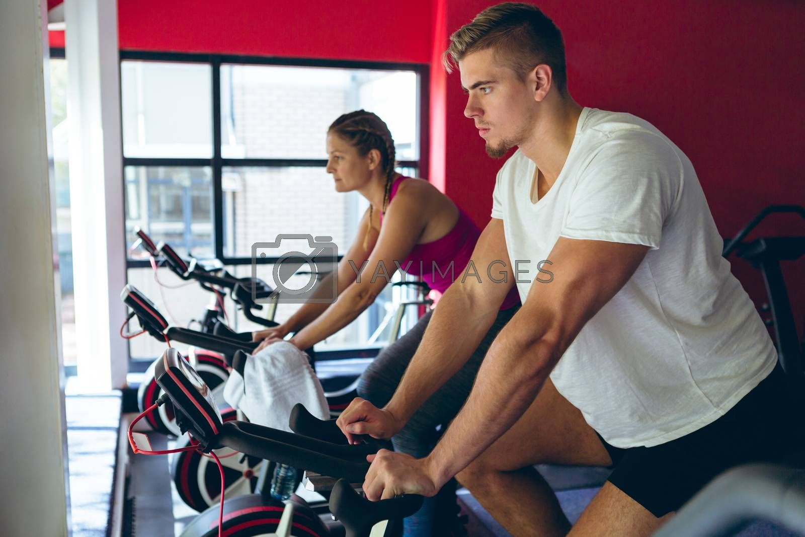 Side view of young Caucasian male and female athlete exercising with exercise bike in fitness center. Bright modern gym with fit healthy people working out and training