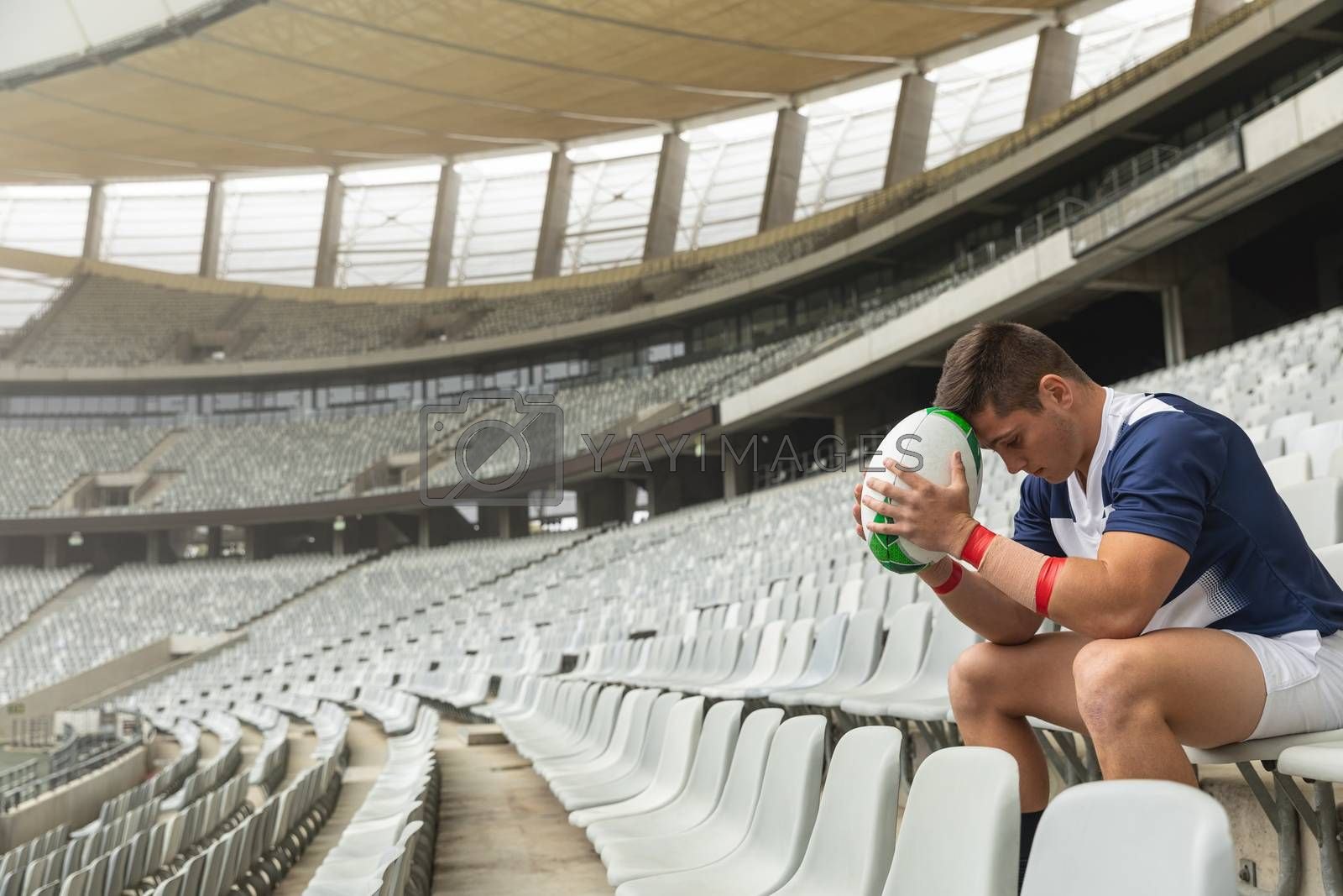 Upset Caucasian Male rugby player sitting with rugby ball in stadium by Wavebreakmedia