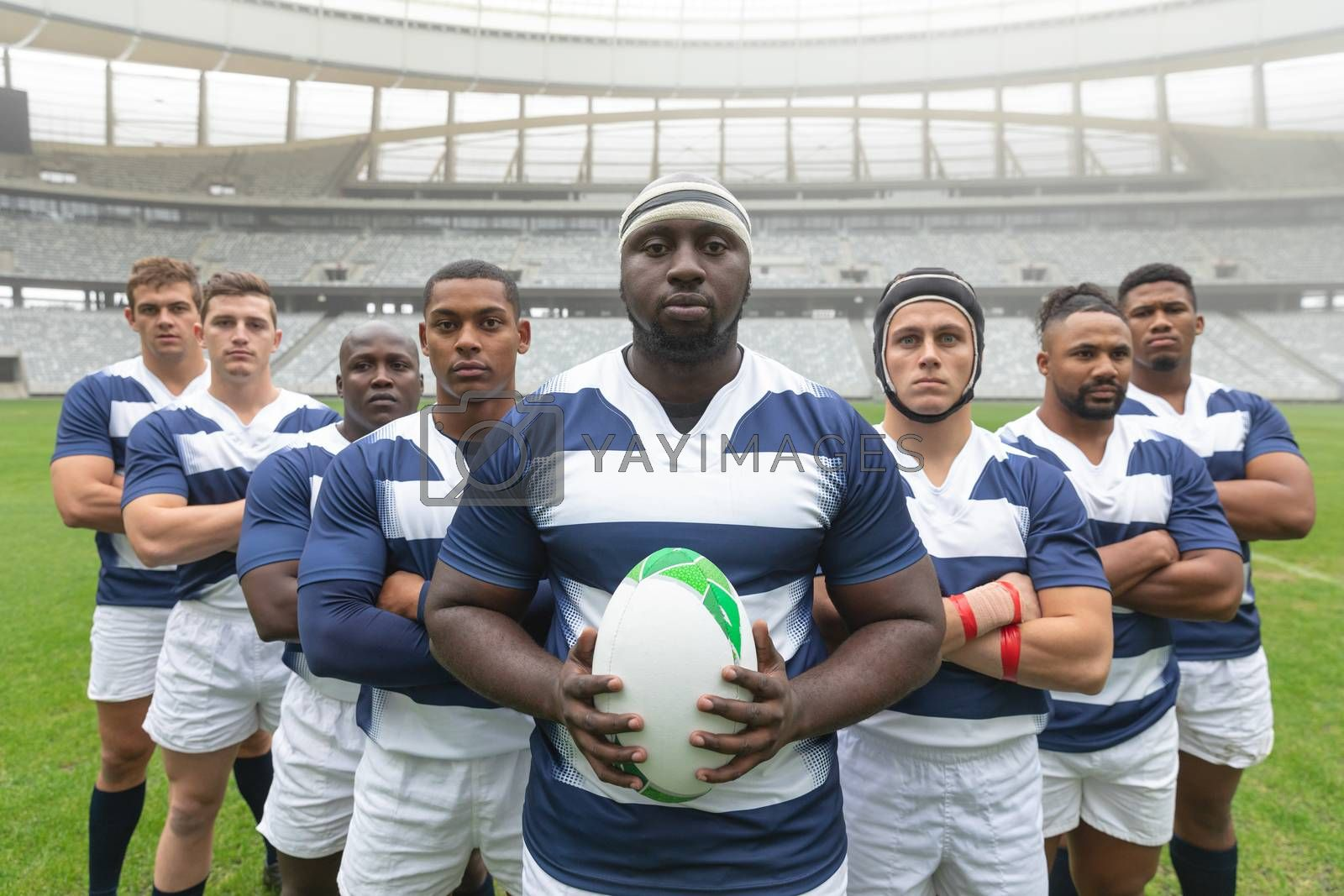 Group of diverse male rugby players standing together with rugby ball in stadium by Wavebreakmedia
