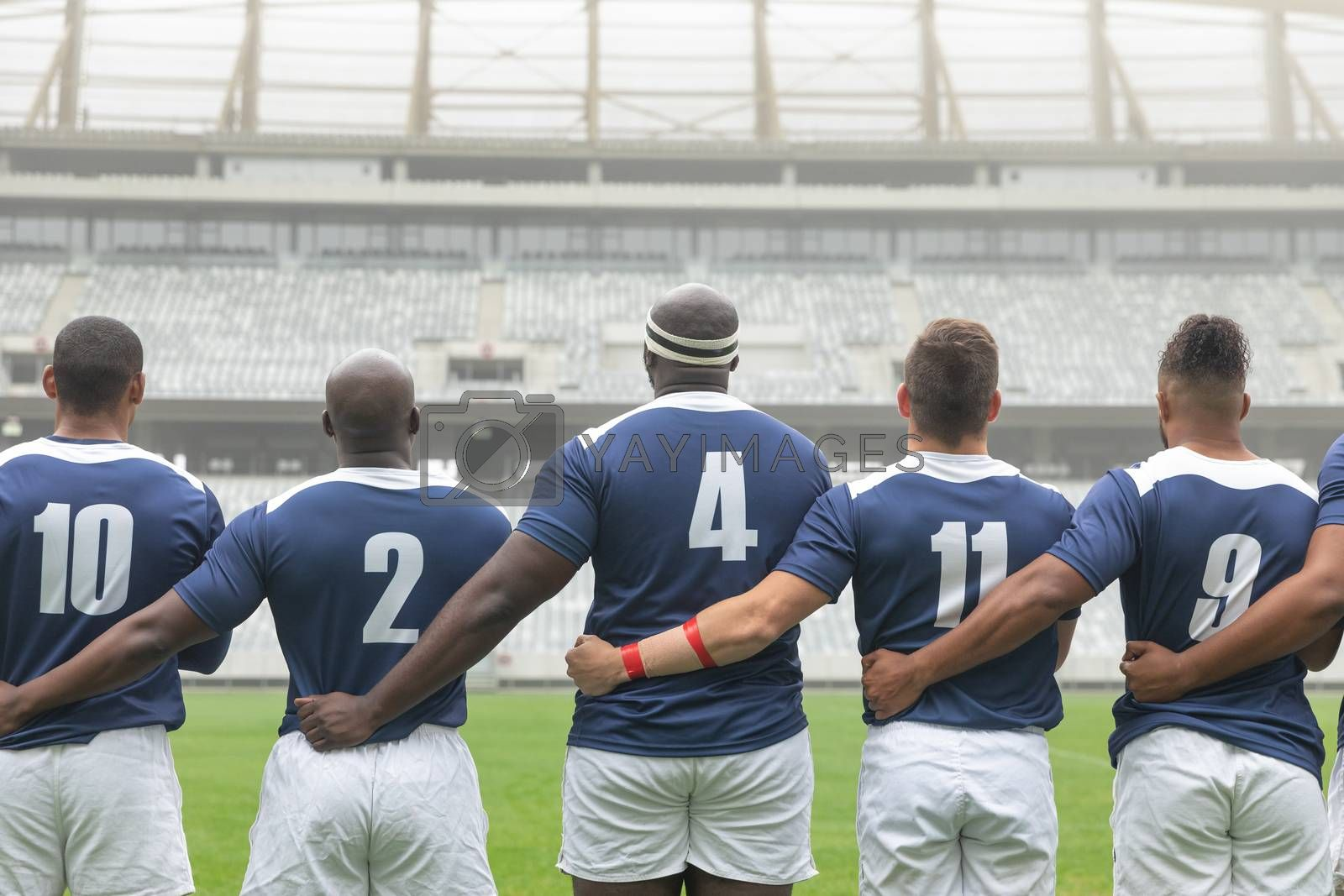 Rear view of group of diverse male rugby players taking pledge together in stadium