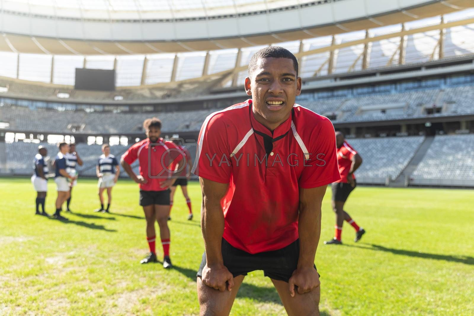 Portrait of tired African American male rugby player standing with hands on his thighs in stadium. Diverse rugby players standing on the rugby field.