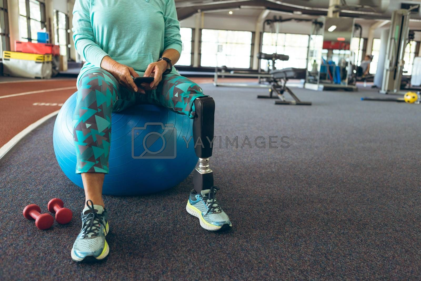 Disabled active senior woman using mobile phone while sitting on exercise ball in fitness center by Wavebreakmedia