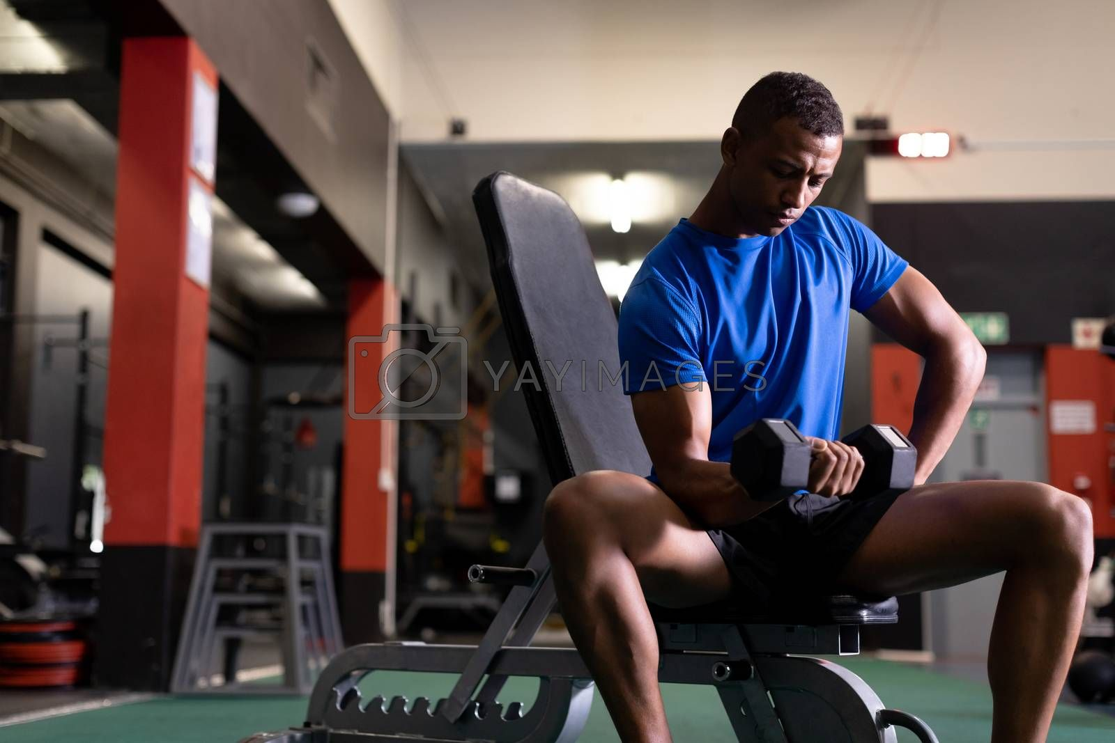 Front view of an African-American man holding a dumbbell while sitting inside a room at a sports centre. Bright modern gym with fit healthy people working out and training. Bright modern gym with fit healthy people working out and training