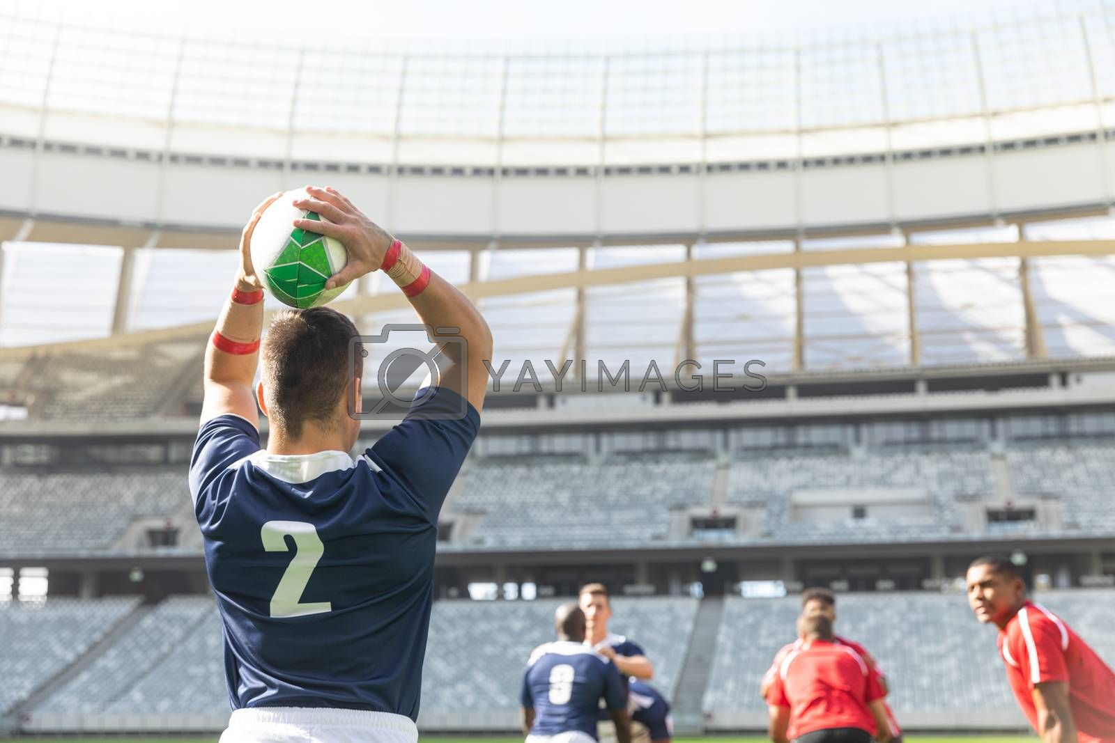 Rear view of Caucasian male rugby player throwing rugby ball while diverse rugby players are waiting for him to throw it in stadium