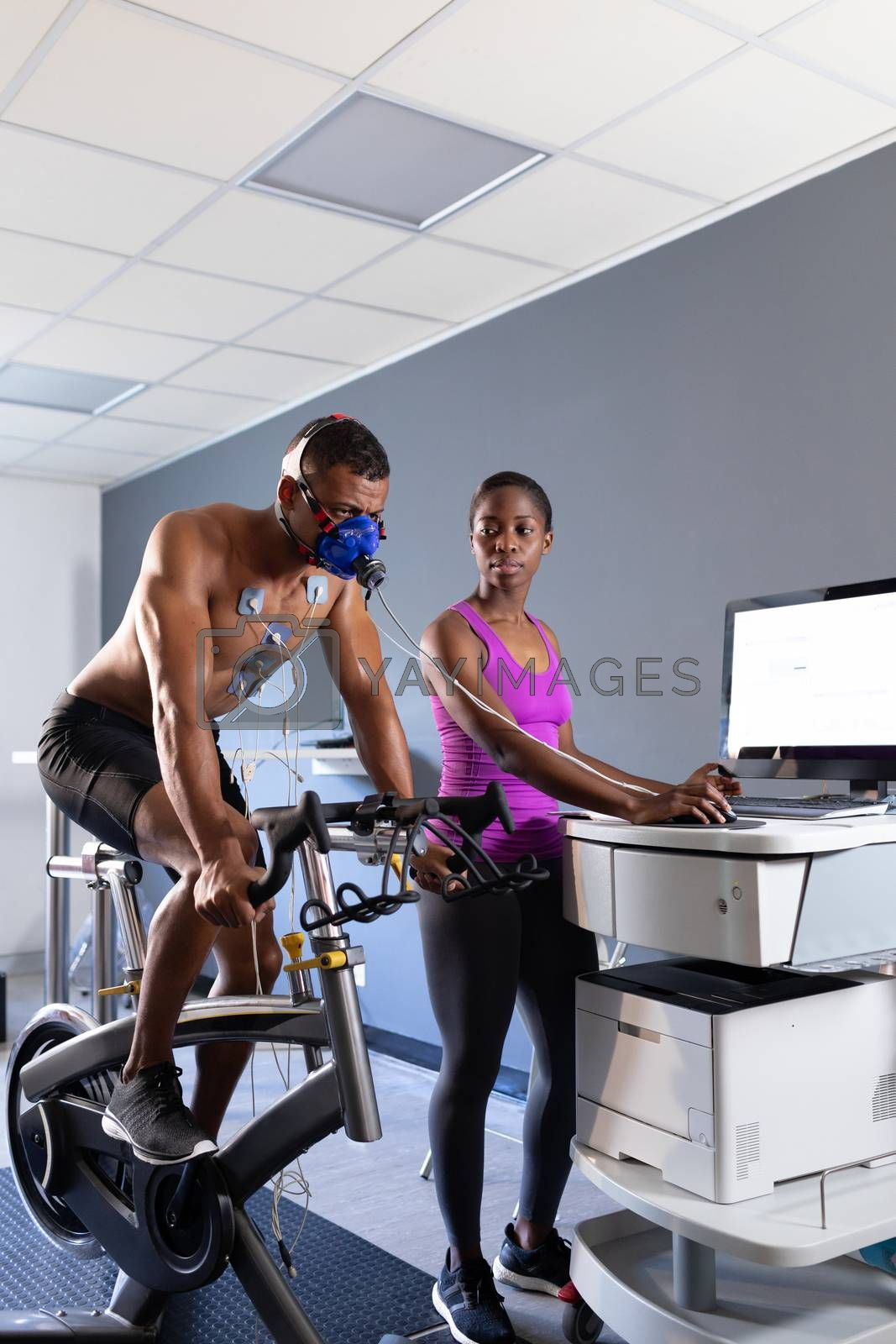Side view of a naked African-American athletic man doing a fitness test using a mask connected to a monitor while riding an exercise bike and an African-American woman assisting him inside a room at a sports center. Bright modern gym with fit healthy people working out and training. Athlete testing themselves with cardiovascular fitness test on exercise bike