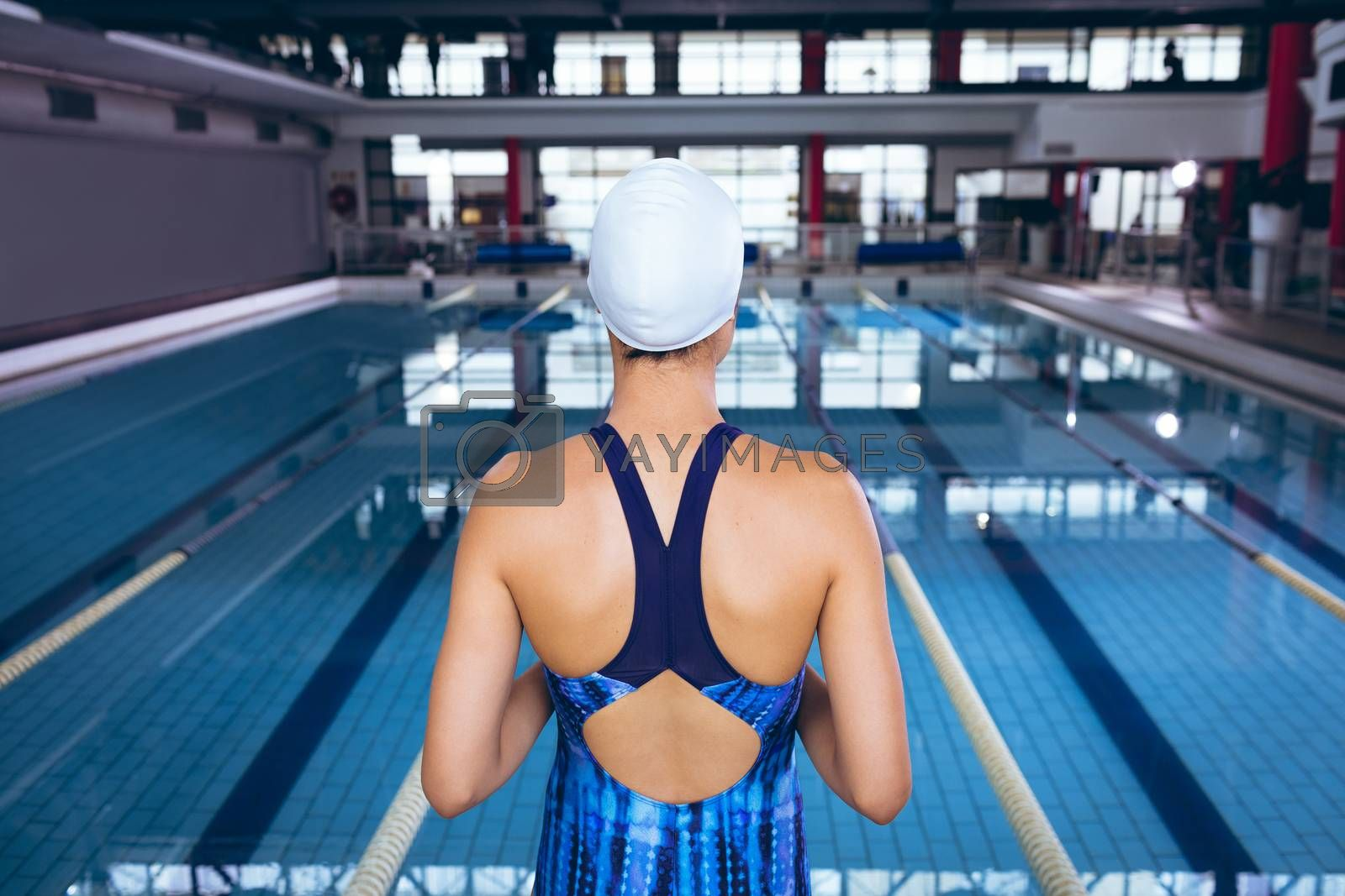 Rear view of a woman wearing a swimsuit and swimming cap standing by an olympic sized pool inside a stadium. Bright modern gym with fit healthy people working out and training