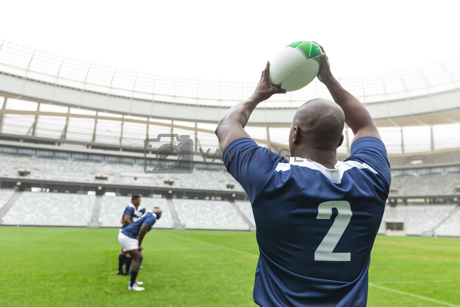 African American male rugby player throwing rugby ball in stadium by Wavebreakmedia