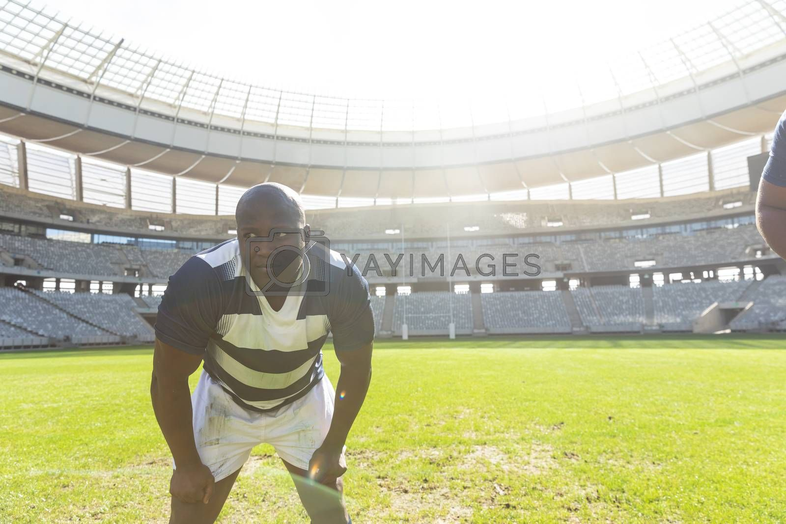 Front view of tired African American male rugby player standing with his hands on thighs in stadium on sunny day.