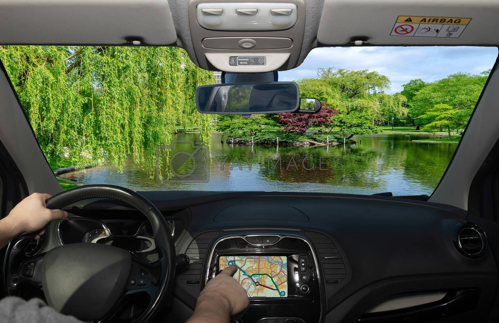 Driving a car while using the touch screen of a GPS navigation system towards the Boston Public Garden, USA