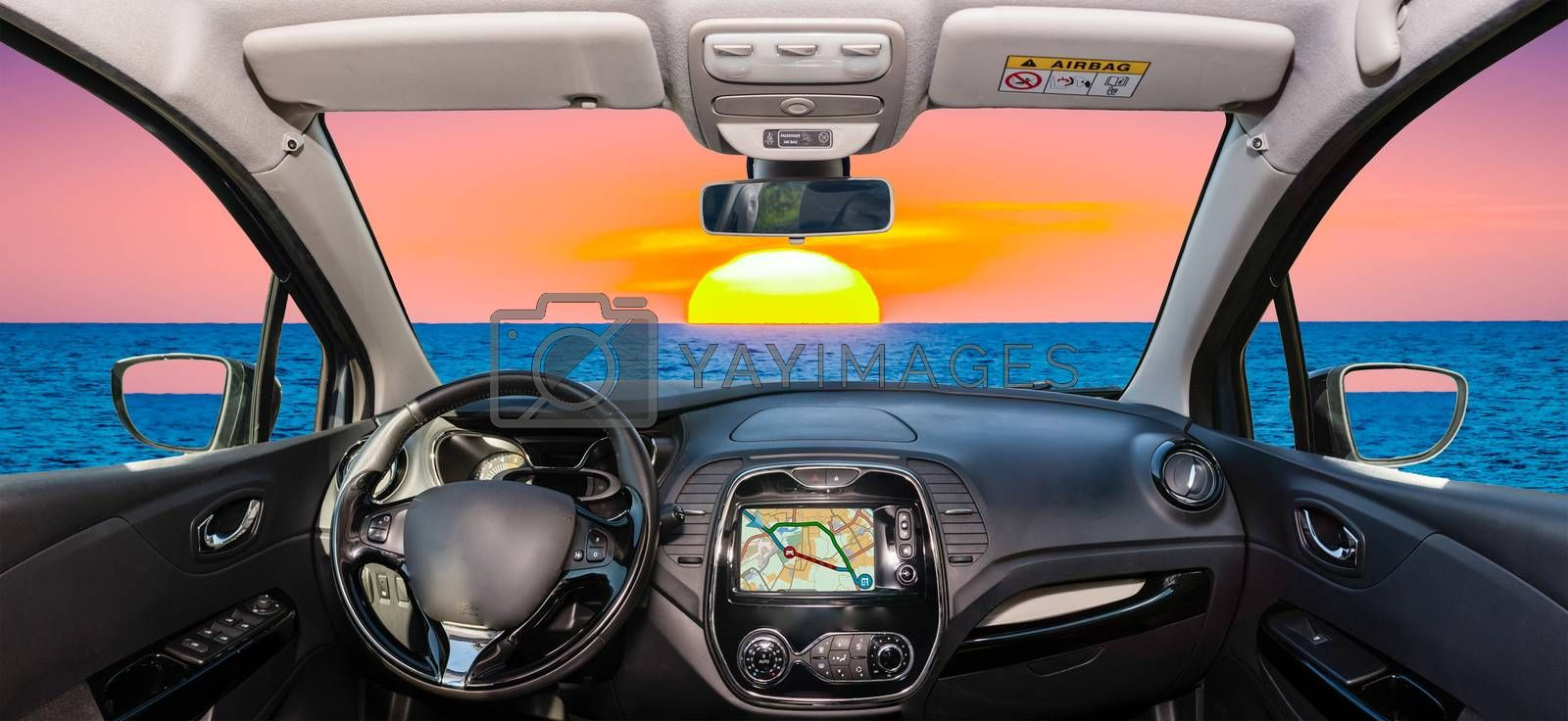 Looking through a car windshield with view of a beautiful sunset by the mediterranean sea, Italy