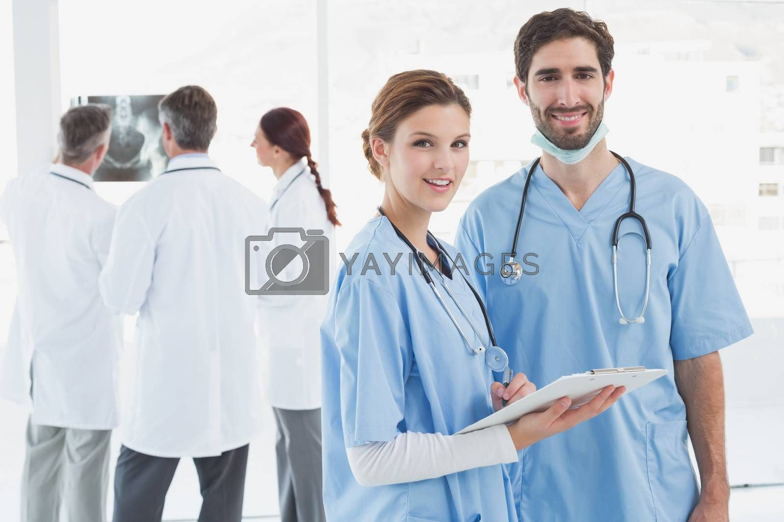 Nurses holding a file together and smiling at the camera
