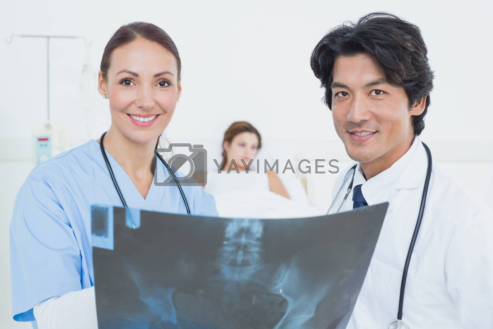 Nurse and doctor with x-ray looking at the camera
