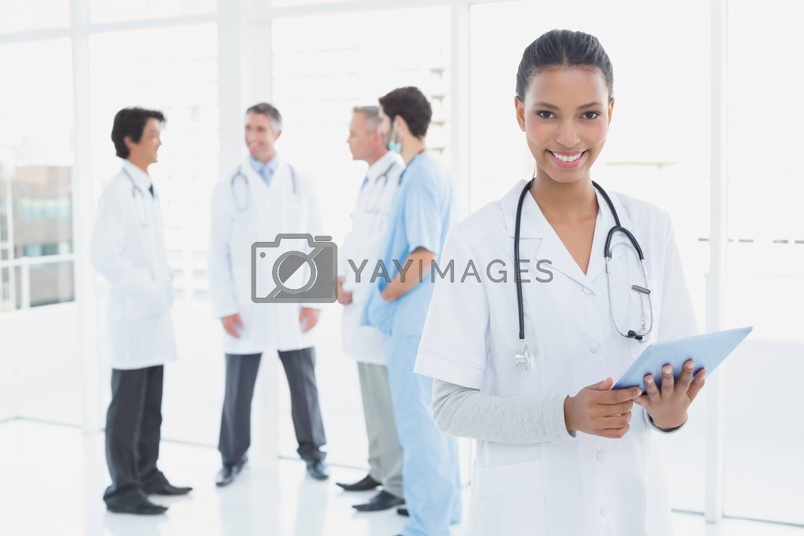 Smiling doctor looking at camera with co-workers behind her