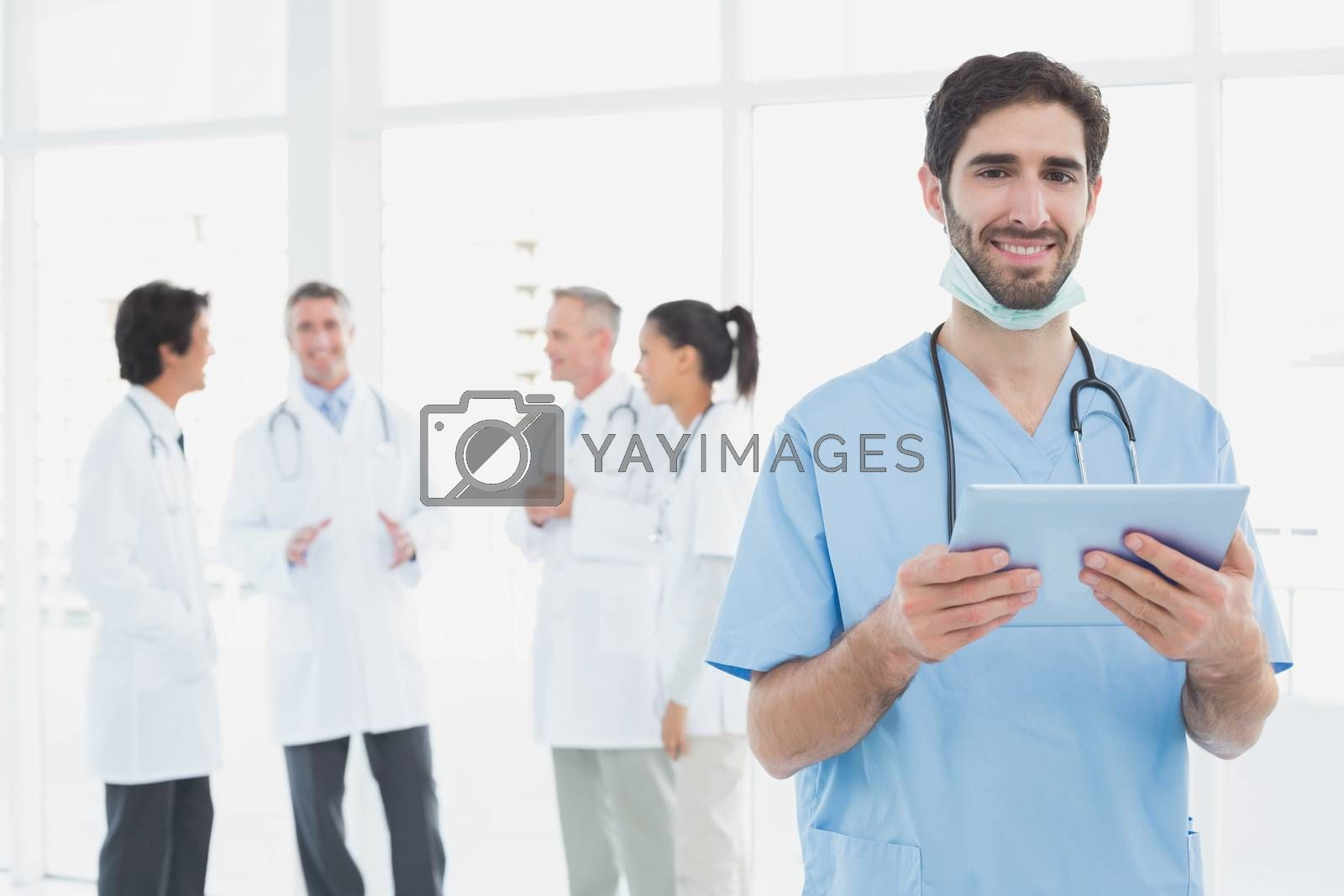 Smiling doctor with a tablet in front of doctors