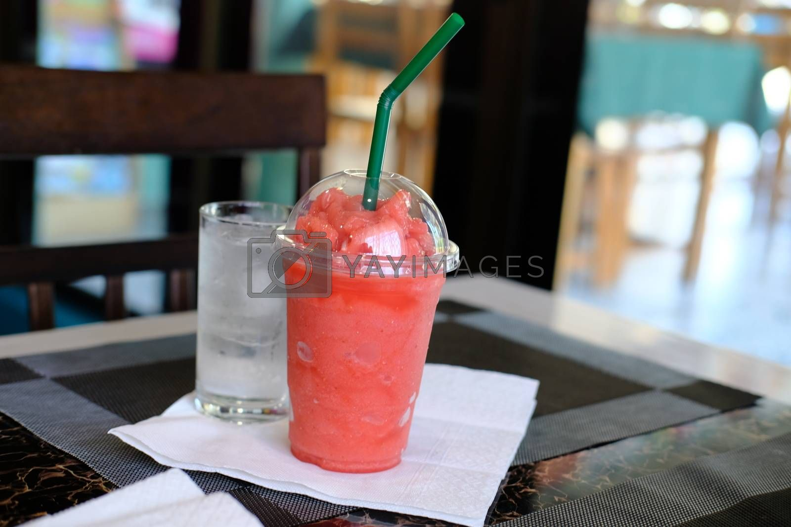 Close-up of Smoothies of watermelon frozen drink in plastic cup and glass of water.