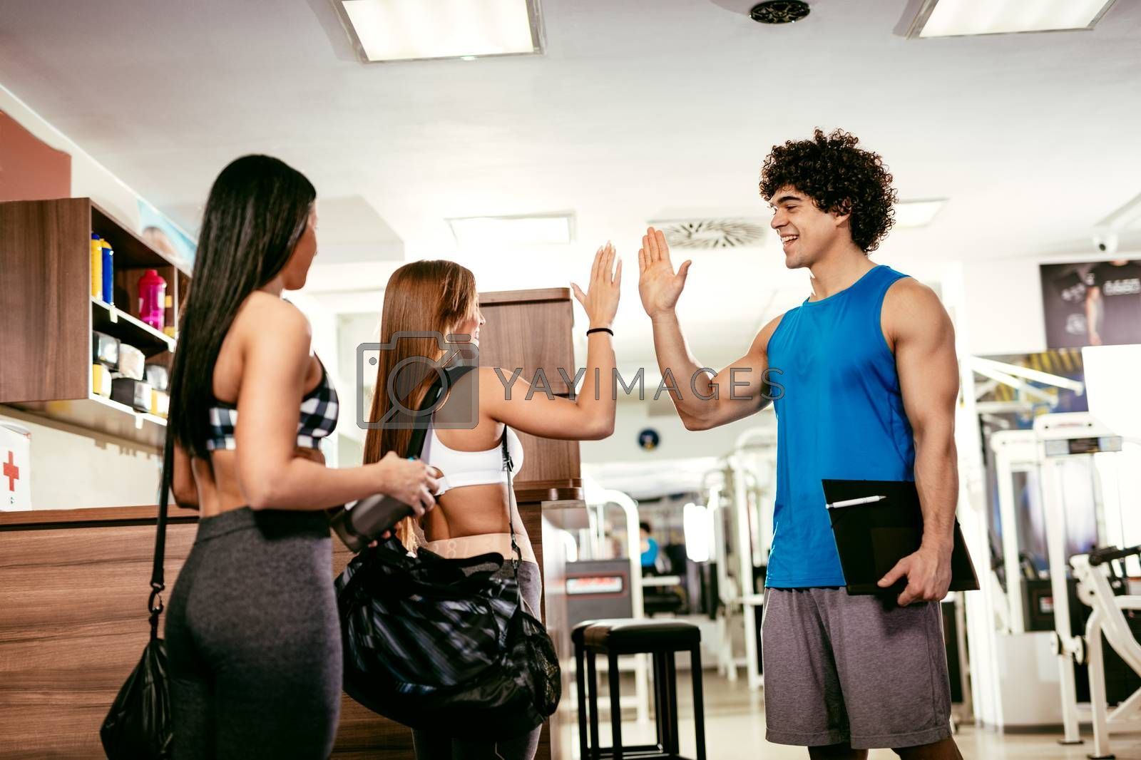 Two happiness female friends greetings with fitness instructor before workout at the gym.