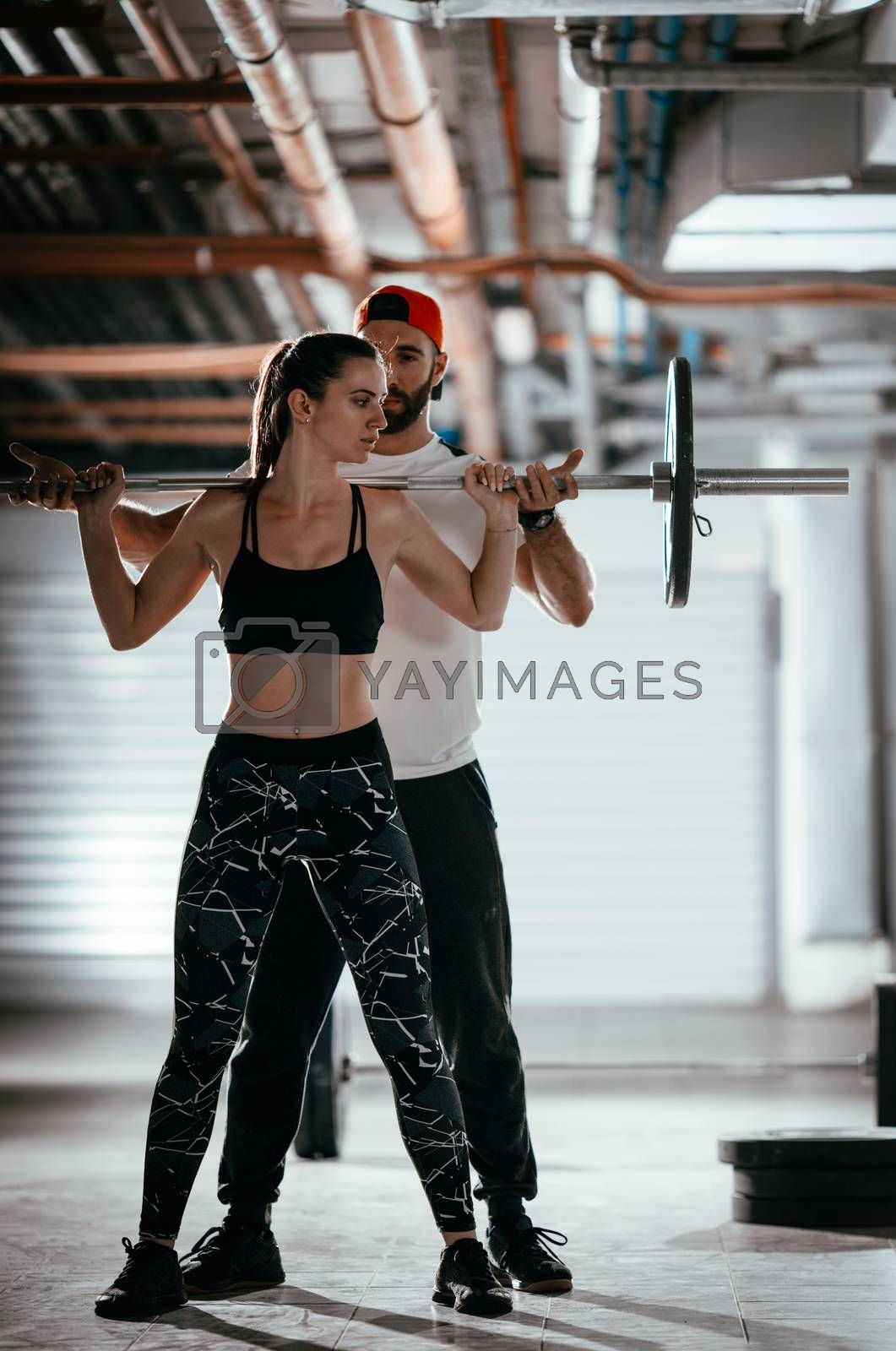 Young muscular woman doing cross workout with a personal trainer at the garage gym.