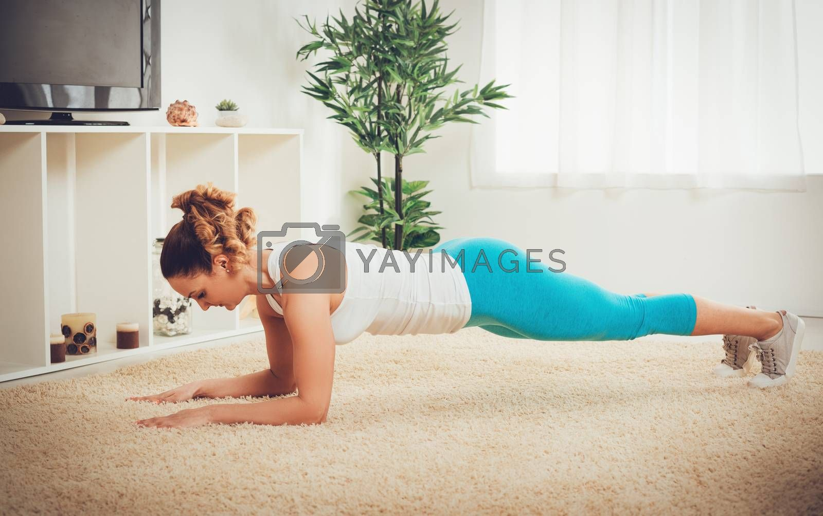 Beautiful muscular girl doing plank exercise at the flat.