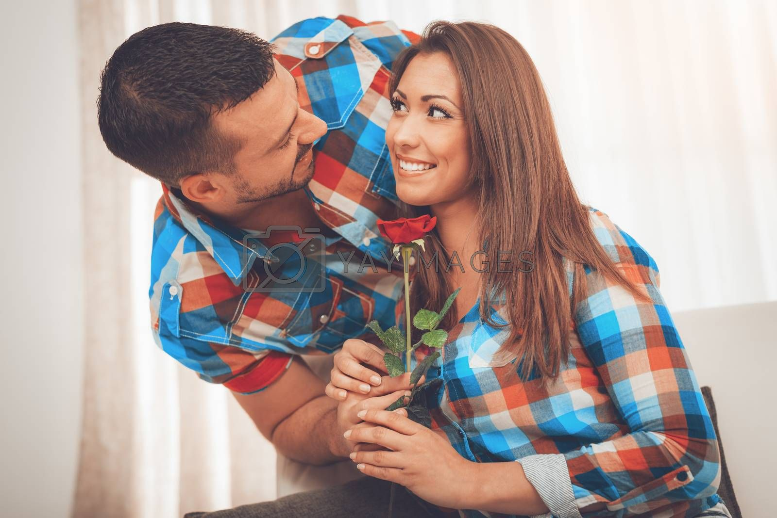 Handsome young man in love give red rose to his girlfriend in an apartment.