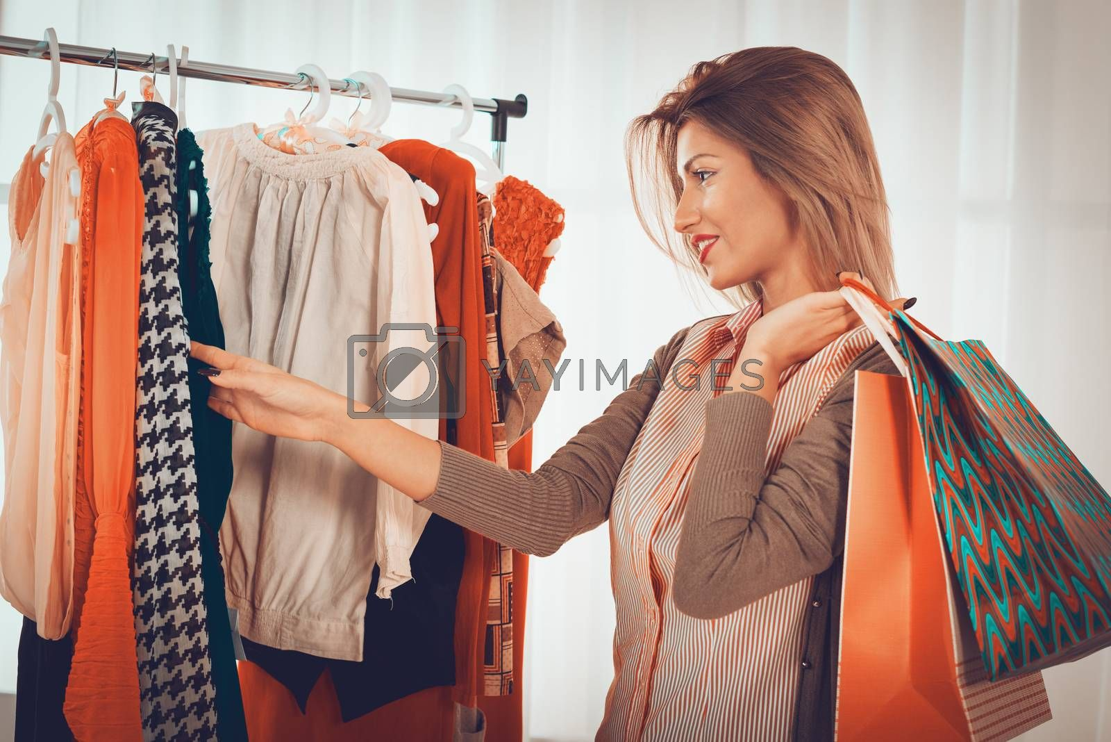 Beautiful young woman choosing clothing at boutique. Looking at camera.