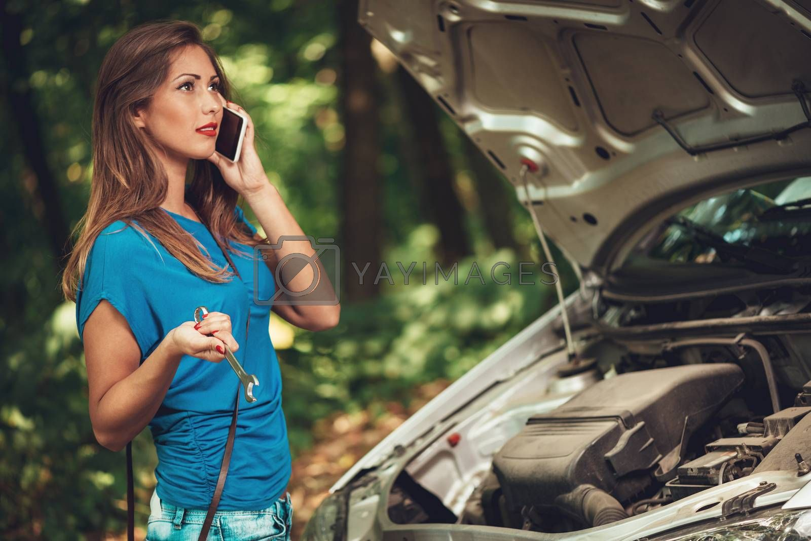 Beautiful young woman with a car that break down on the road in forest. She has standing by a car, holding wrench and talking at mobile phone.