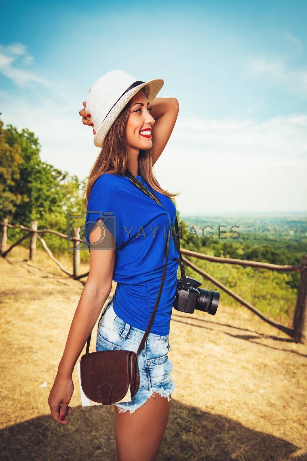 Pretty young woman standing by viewpoint and holding digital camera.